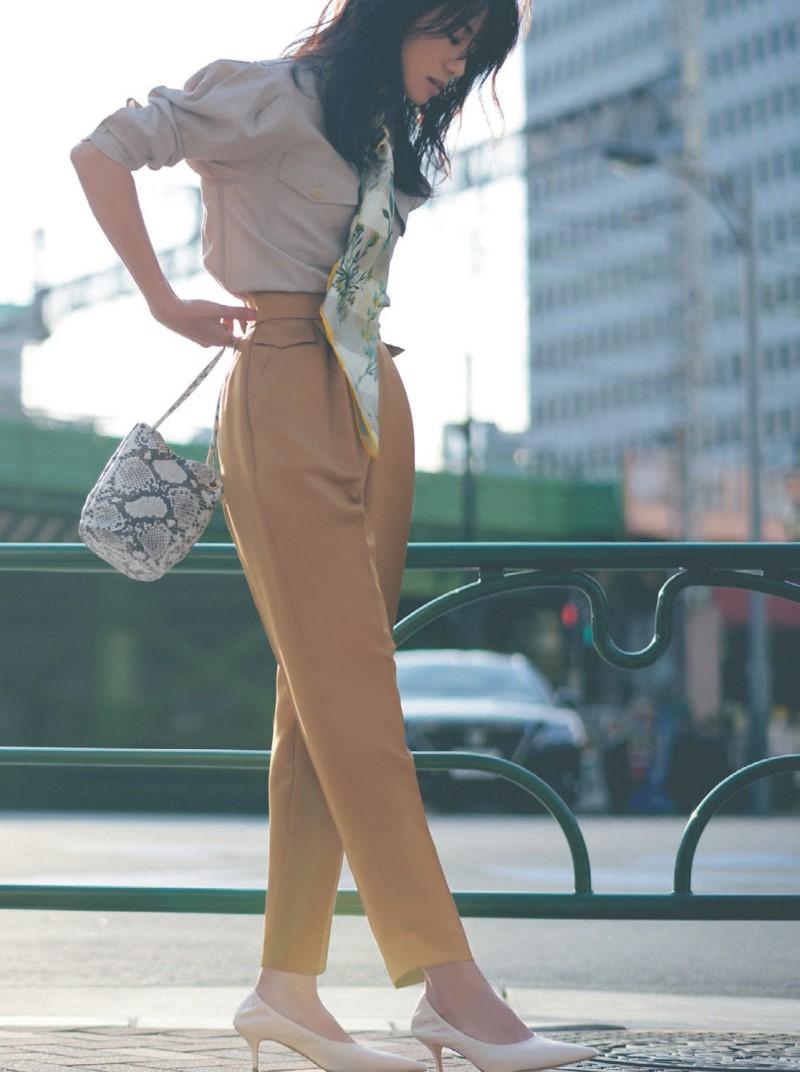 東原亜希さんの画像です。ベージュのシャツにハイウェストのパンツを着ています。通勤服です。